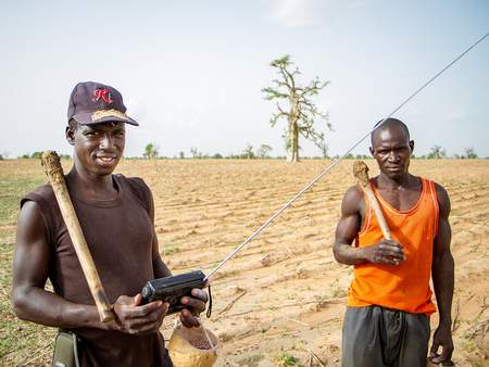 Farmers in the Sahelian village of Diouna in southern Mali listen to the radio as they prepare their field for planting. The radio remains an important tool for the exchange of information and services. Photo: F. Fiondella.