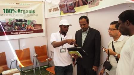 Naabeh Andrews montrant à des visiteurs une vidéo sur le cycle de production de l'engrais Coco Peat.