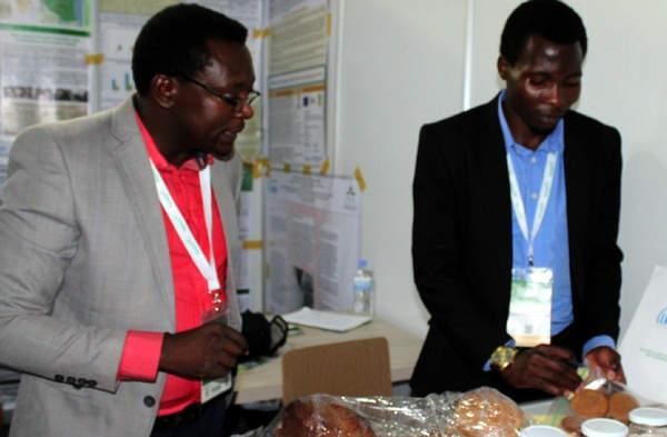 Léon Niyibisys (gauche) explique à un étudiant comment exposer son produit